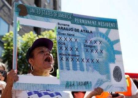 A woman holds a replica green card sign during a protest march to demand immigration reform in Hollywood