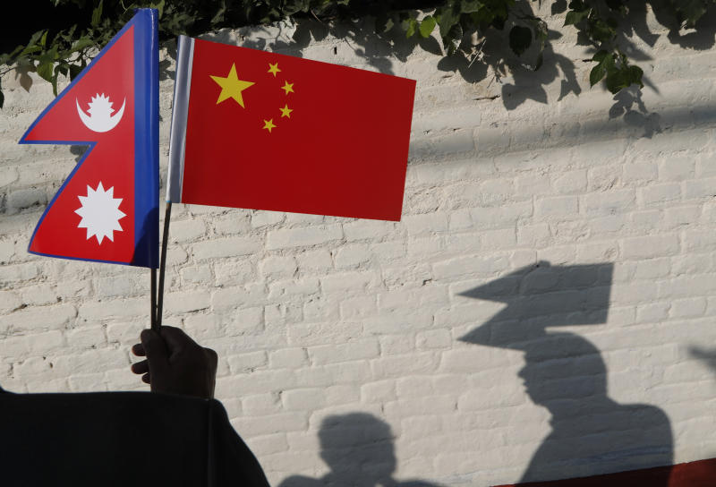 A Nepalese man holds Chinese and Nepalese flags as he waits to welcome Chinese president Xi Jinping in Kathmandu, Nepal, Saturday, Oct 12, 2019. Xi arrived Saturday from New Delhi, where he met with Indian Prime Minister Narendra Modi. He was received by Nepalese President Bidhya Devi Bhandari and Prime Minister K.P. Sharma Oli at the Kathmandu airport. (AP Photo/Niranjan Shrestha)