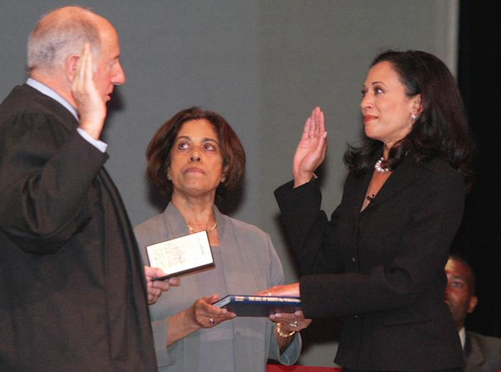 """San Francisco's new district attorney, Kamala Harris, right, receives the oath of office from California Supreme Court Chief Justice Ronald M. George, left, during inauguration ceremonies Thursday, Jan. 8, 2004, in San Francisco. In the center is Harris' mother, Dr. Shyamala Gopalan, who holds a copy of """"The Bill of Rights."""" (George Nikitin/AP)"""