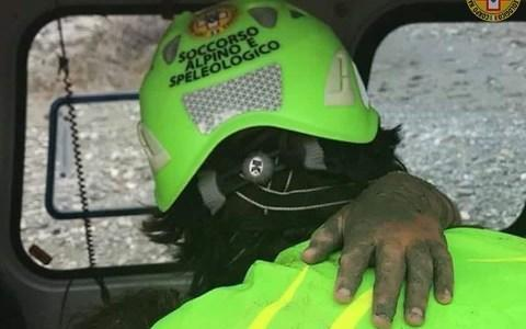 <span>The hand of the eight year old girl on the shoulder of an alpine rescue specialist</span> <span>Credit: Twitter </span>