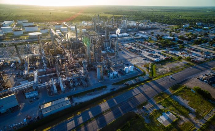 A refinery casts long shadows as the sun sets in the background.