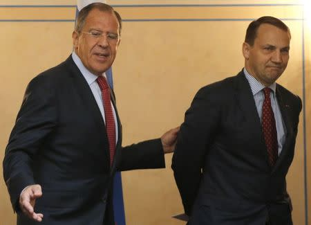 Russian Foreign Minister Sergei Lavrov (L) shows the way to his Polish counterpart Radoslaw Sikorski as they attend a news conference after their meeting his German counterpart Frank-Walter Steinmeier in St. Petersburg, June 10, 2014. REUTERS/Alexander Demianchuk