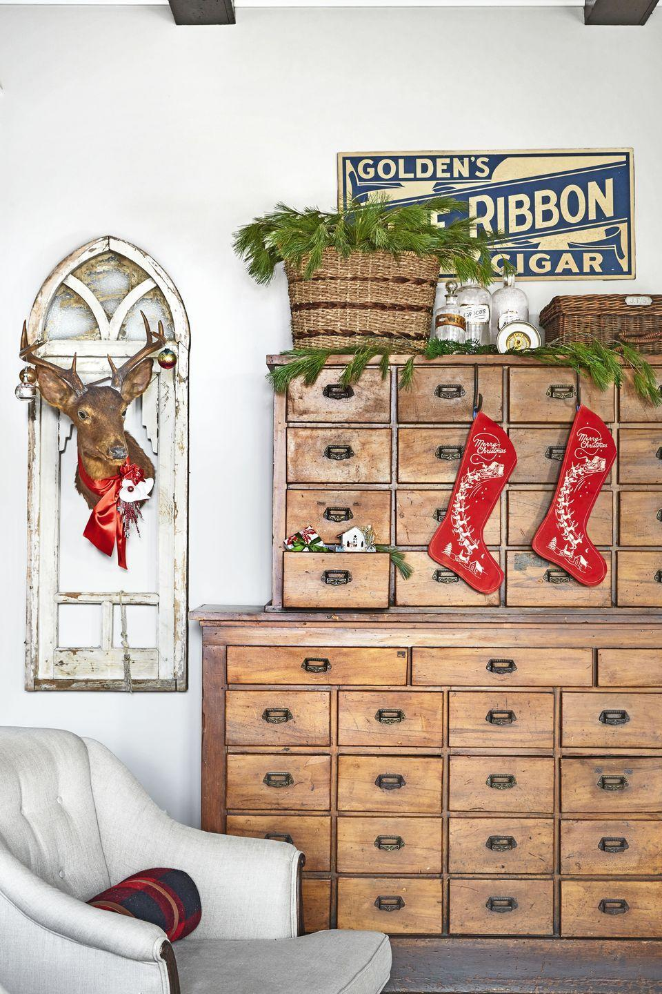 """<p>Make dressers, armoires, and other storage pieces fit for a visit from Santa by <a href=""""https://www.countryliving.com/shopping/g1407/personalized-christmas-stockings/"""" rel=""""nofollow noopener"""" target=""""_blank"""" data-ylk=""""slk:hanging stockings"""" class=""""link rapid-noclick-resp"""">hanging stockings</a> from their pulls and drawers. </p><p><a class=""""link rapid-noclick-resp"""" href=""""https://www.amazon.com/Solucky-Classic-Christmas-Stockings-Decorations/dp/B075S1WMRC/?tag=syn-yahoo-20&ascsubtag=%5Bartid%7C10050.g.1247%5Bsrc%7Cyahoo-us"""" rel=""""nofollow noopener"""" target=""""_blank"""" data-ylk=""""slk:SHOP STOCKINGS"""">SHOP STOCKINGS</a></p>"""