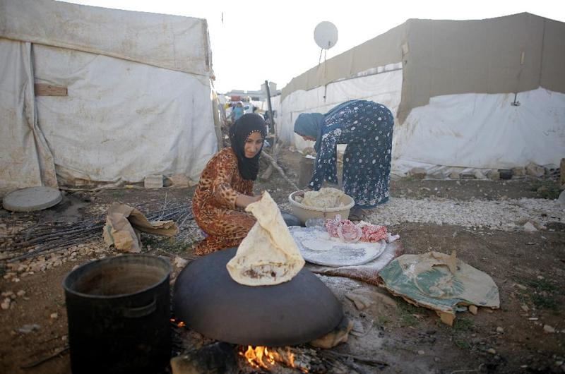 A handout picture released by Caritas Internationalis shows Syrian women preparing food at a refugee camp in in the Lebanese village of Zahle in the Bekaa valley, on June 18, 2014 (AFP Photo/Matthieu Alexandre)