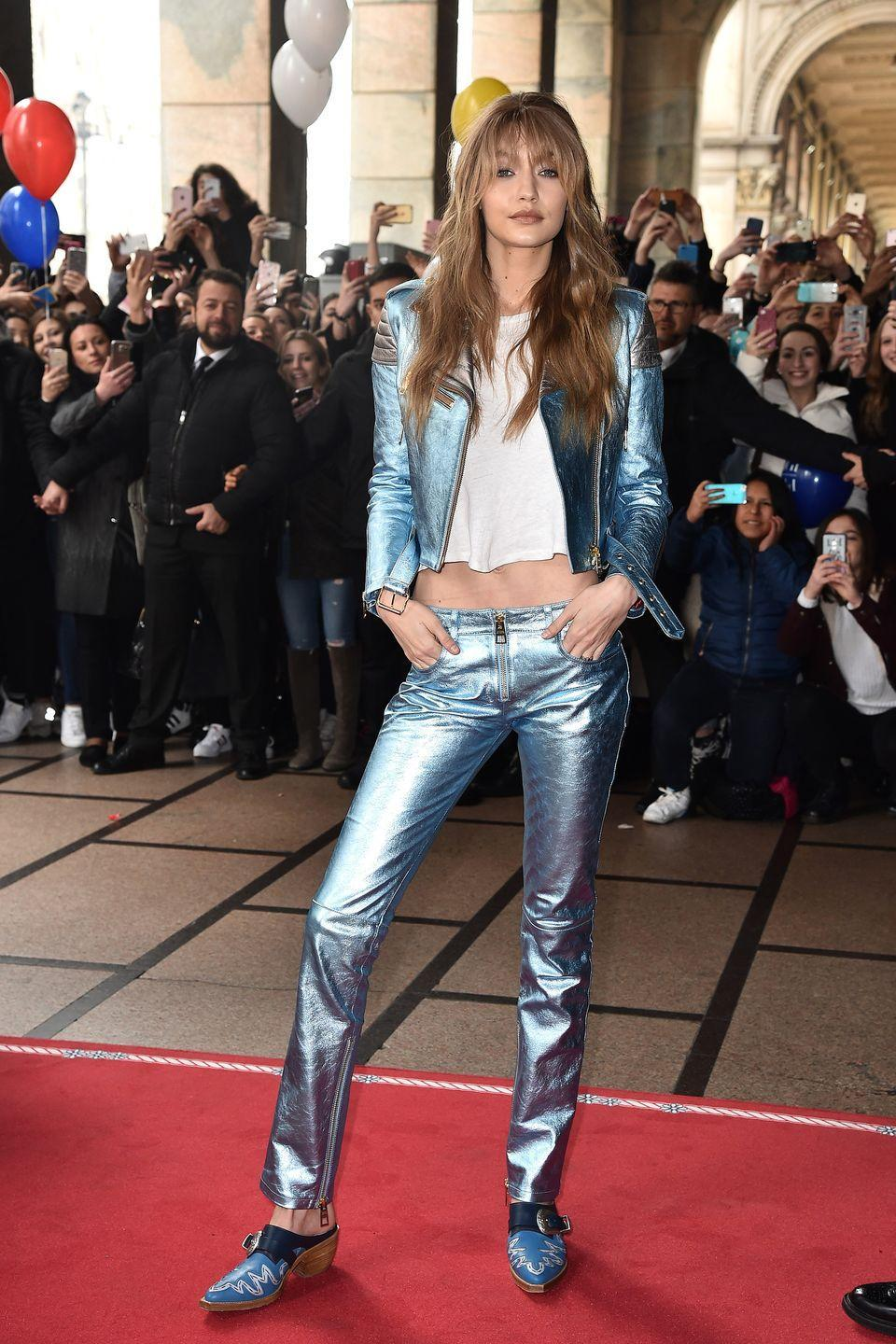 <p>In a metallic light blue leather jacket and pants, white tee, Western style mules and chunky bangs while promoting Tommy x Gigi Spring 2017 during Milan Fashion Week.</p>