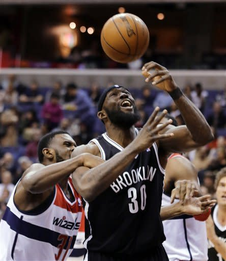 Washington Wizards forward Chris Singleton (31) grabs the arm of Brooklyn Nets forward Reggie Evans (30) as Evans tries to shoot during the first half of an NBA basketball game Friday, Feb. 8, 2013, in Washington. (AP Photo/Alex Brandon)