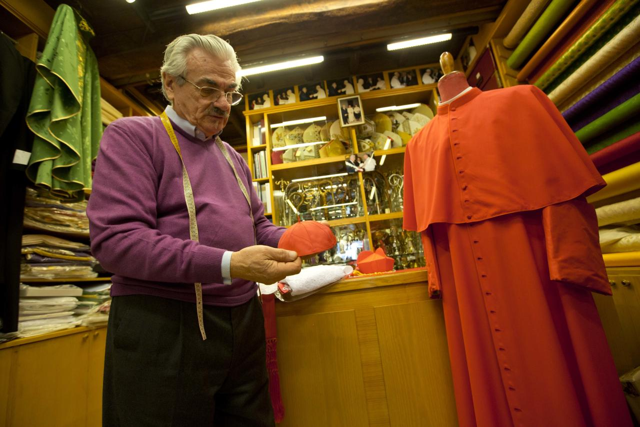 "Raniero Mancinelli shows a cardinal's skull cap in his tailor shop in Rome, Thursday Feb. 13, 2014. No glitzy gold, no rich velvet, no regal fur but rather sensible black shoes and a white cassock so flimsy you can see his black trousers through it. Pope Francis has pared down the papal wardrobe to fit his call for simplicity and humility among his clergy. The pope's personal style _ which earned him Esquire magazine's ""Best Dressed Man of 2013"" award _ and his broader message of sobriety will be put to the test Saturday when he inducts 19 prelates into the College of Cardinals, placing the three-cornered red silk biretta on the heads of the new ""princes of the church."" (AP Photo/Alessandra Tarantino)"