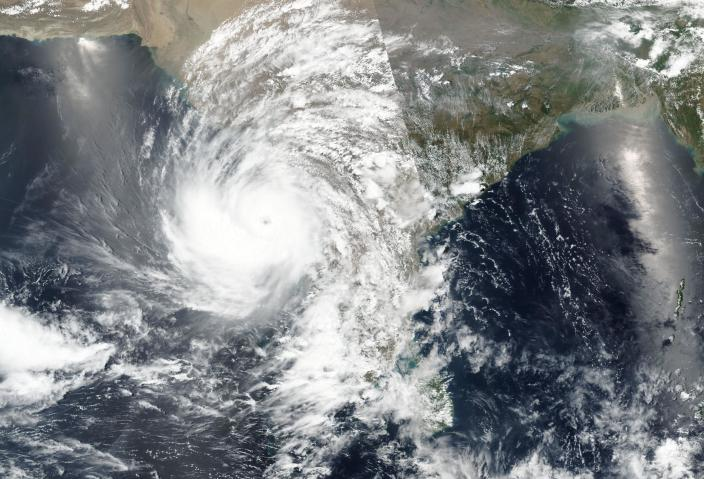 This Sunday, May 16, 2021, satellite image released NASA shows a cyclone approaching western India. A severe cyclone is roaring in the Arabian Sea off southwestern India with winds of up to 140 kph (87 mph), already causing heavy rains and flooding that have killed multiple people, officials said Sunday. Cyclone Tauktae, the season's first major storm, is expected to make landfall early Tuesday in Gujarat state, a statement by the India Meteorological Department said. (NASA Worldview, Earth Observing System Data and Information System (EOSDIS) via AP)