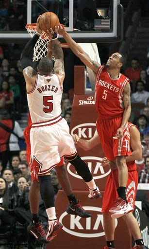 Houston Rockets guard Courtney Lee, right, blocks the shot of Chicago Bulls forward Carlos Boozer during the first half of an NBA basketball game Monday, April 2, 2012, in Chicago. (AP Photo/Charles Rex Arbogast)