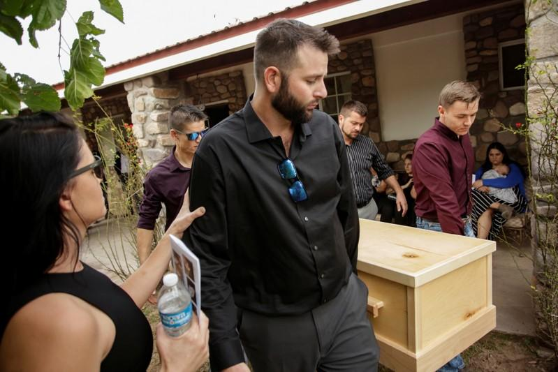 Howard Miller and his relatives carry one of the coffins of his wife Rhonita Miller and children Howard, Kristal, Titus, and Teana, who were killed by unknown assailants, during their funeral service in La Mora