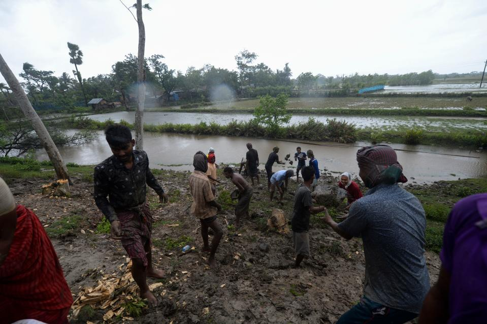 Villagers reinforce an embankment with sacks of soil ahead of the expected landfall of cyclone Amphan, in Dacope on May 20, 2020. (Photo by MUNIR UZ ZAMAN/AFP via Getty Images)
