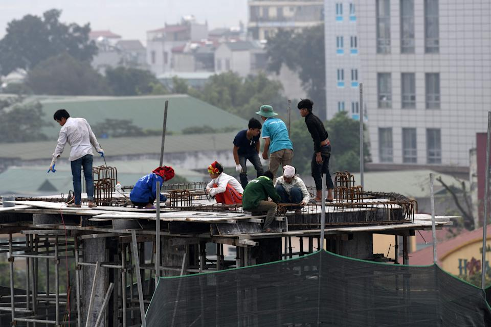 Laborers work at a construction of a low rise building in Hanoi on April 20, 2018. (Photo: ROSLAN RAHMAN/AFP/Getty Images)