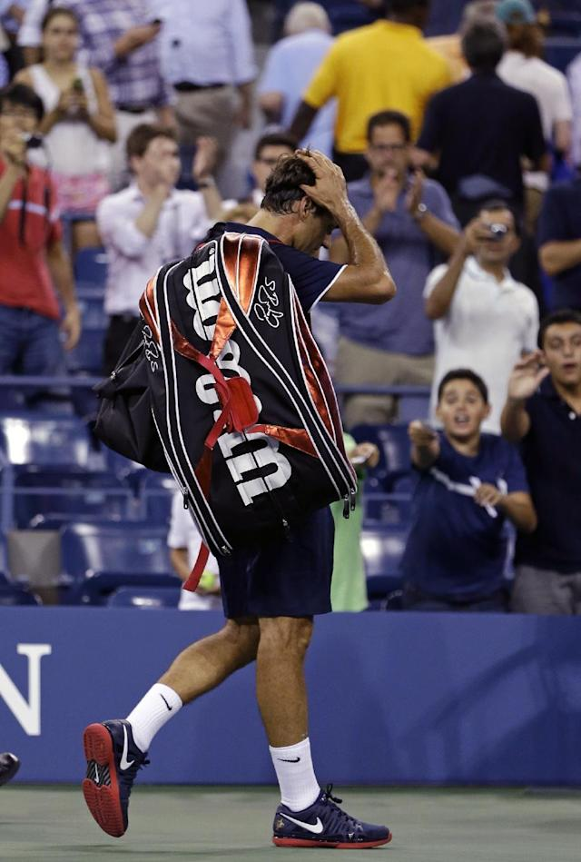 Roger Federer, of Switzerland, leaves the court after being defeated by Tomas Berdych, of the Czech Republic, in a quarterfinals match at the U.S. Open tennis tournament on Wednesday, Sept. 5, 2012, in New York. Berdych won 7-6 (1), 6-4, 3-6, 6-3. (AP Photo/Darron Cummings)