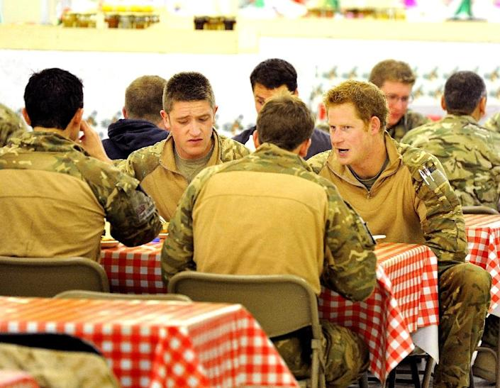 Prince Harry sits with fellow air-crew members at the dining facility in Camp Bastion in Afghanistan's Helmand province, December 11, 2012 (AFP Photo/John Stillwell)