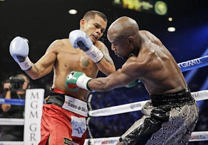 Marcos Maidana punches Floyd Mayweather during their WBA and WBC title fight. (AP)