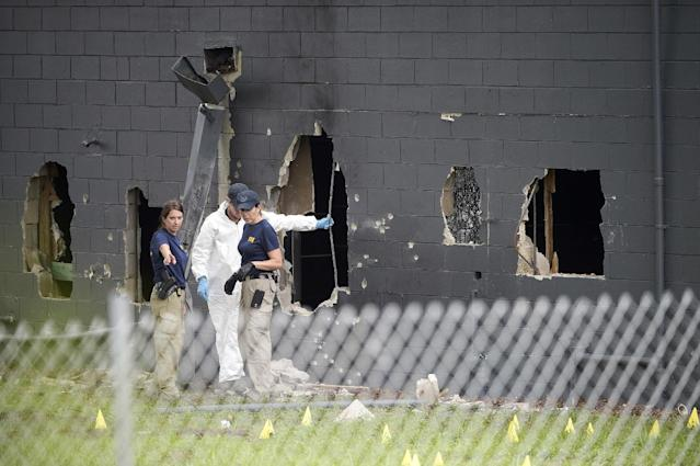 <p>Police officials investigate the back of the Pulse nightclub after a shooting involving multiple fatalities at the nightclub in Orlando, Fla., June 12, 2016. (AP Photo/Phelan M. Ebenhack) </p>