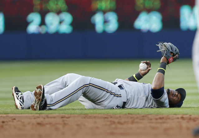 Milwaukee Brewers shortstop Jean Segura (9) lies on the field after being injured fielding a ball in the third inning of a baseball game against Atlanta Braves Wednesday, May 21, 2014 in Atlanta. Segura remained in the game. (AP Photo/John Bazemore)