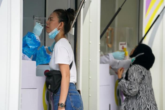 Healthcare workers take nasal swab samples from local residents for a COVID-19 test in Bangkok