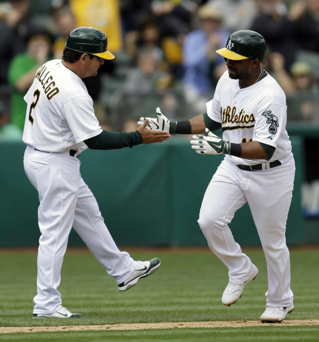 Oakland Athletics' Alberto Callaspo, right, is congratulated by third base coach Mike Gallego after hitting a 2-run home run off Cleveland Indians starting pitcher Corey Kluber in the third inning of a baseball game on Wednesday, April 2, 2014, in Oakland, Calif. (AP Photo/Ben Margot)