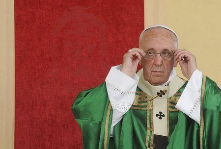 Pope Francis adjusts his glasses in front of his chair, which has an image of the Shroud of Turin woven into the red fabric, as he leads a mass during a two-day pastoral visit in Turin, Italy, June 21, 2015. REUTERS/Giorgio Perottino