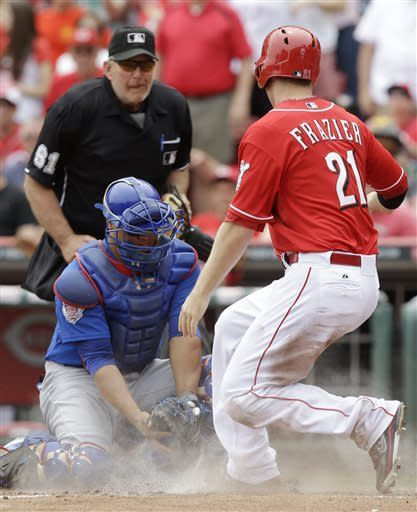 Cincinnati Reds' Todd Frazier (21) scores on a single by Ryan Hanigan as Chicago Cubs catcher Welington Castillo is late with the tag in the fourth inning of the MLB National League baseball game, Sunday, May 26, 2013, in Cincinnati. (AP Photo/Al Behrman)