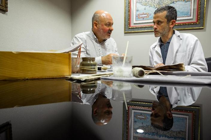 Artistic editor, Juan Jose (left) and quality control operator of Spanish publishing Siloe Luis Miguel work on cloning the illustrated codex hand-written manuscript Voynich in Burgos on August 9, 2016 (AFP Photo/Cesar Manso)