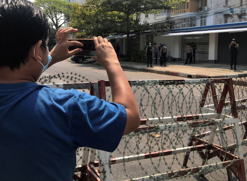 A journalist and a police officer take pictures of each other as people protest against the military coup in Yangon, Myanmar