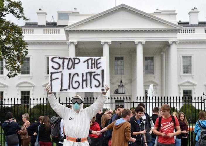A man dressed in a protective suit and mask holds a poster demanding a halt of all flights from West Africa, as he protests outside the White House in Washington, DC on October 16, 2014 (AFP Photo/Mladen Antonov)