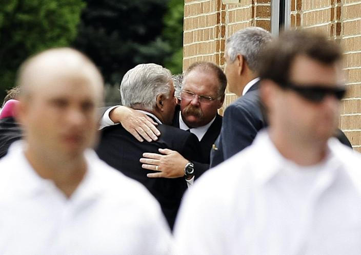 Andy Reid, center, is embraced after the funeral for his son Garrett Reid in Broomall, Pa., in August 2012.