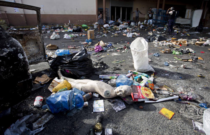 <p>A mannequin lies amid merchandise scattered across the parking lot of a burned and looted Delimart supermarket complex after two days of protests against a planned hike in fuel prices in Port-au-Prince, Haiti, Sunday, July 8, 2018. (Photo: Dieu Nalio Chery/AP) </p>