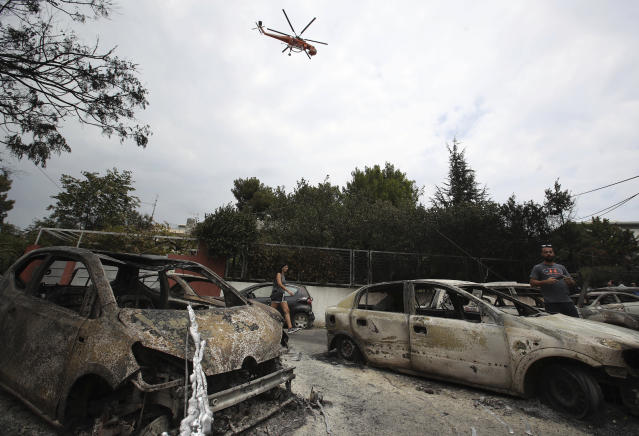 <p>A firefighting helicopter flies above burned-out cars in Mati east of Athens, Tuesday, July 24, 2018. (Photo: Thanassis Stavrakis/AP) </p>