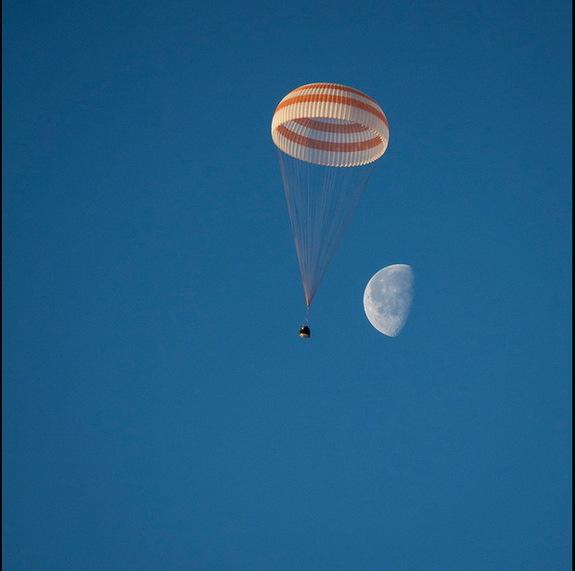 The half-moon is captured behind a Soyuz spacecraft returning three crewmembers to Earth from the International Space Station on March 11, 2014.