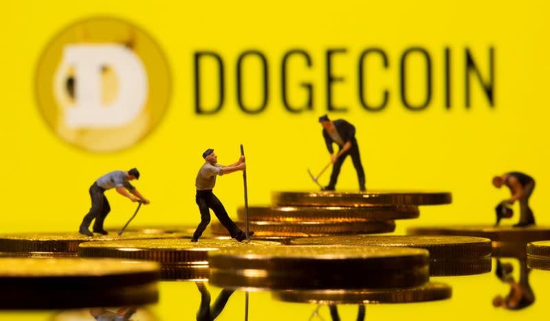 Small toy figures are seen on the cryptocurrency representation with Dogecoin logo in the background in this illustration