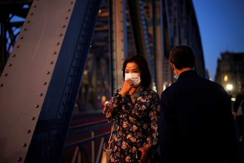 FILE PHOTO: People wearing face masks are seen on a street amid the global outbreak of the coronavirus disease (COVID-19) in Shanghai