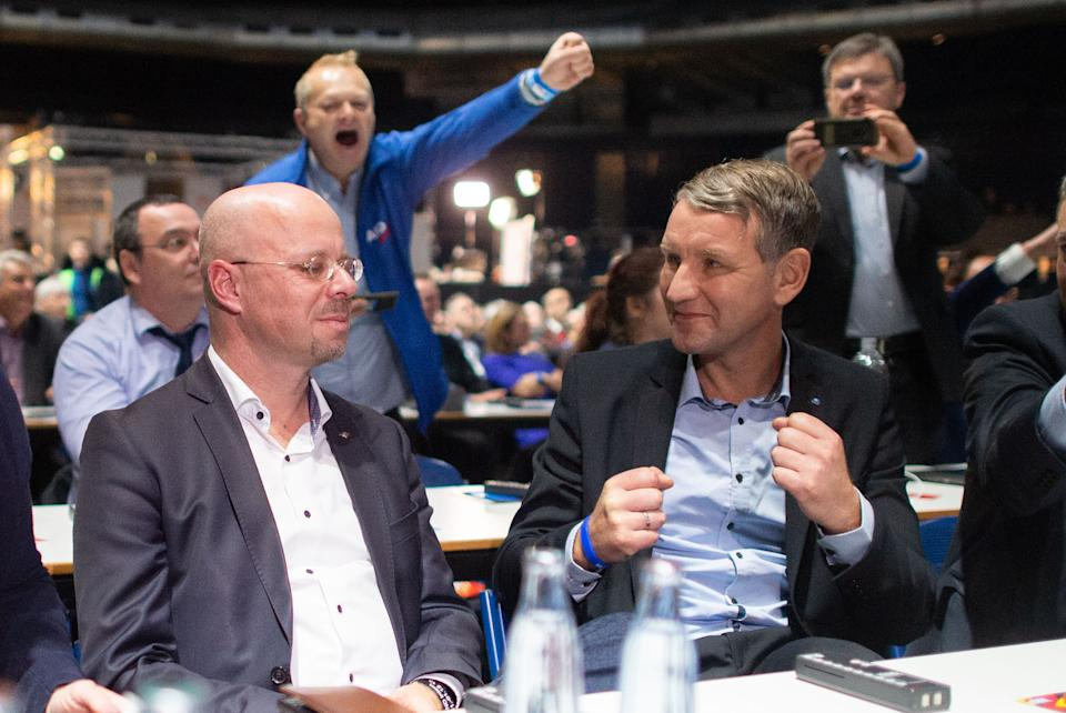 01 December 2019, Lower Saxony, Brunswick: Björn Höcke (front right), regional chairman of AfD Thuringia, is pleased at the AfD party conference after the election of Andreas Kalbitz (front left), regional chairman of AfD Brandenburg, as an associate member of the federal executive committee of AfD. Photo: Hauke-Christian Dittrich/dpa (Photo by Hauke-Christian Dittrich/picture alliance via Getty Images)