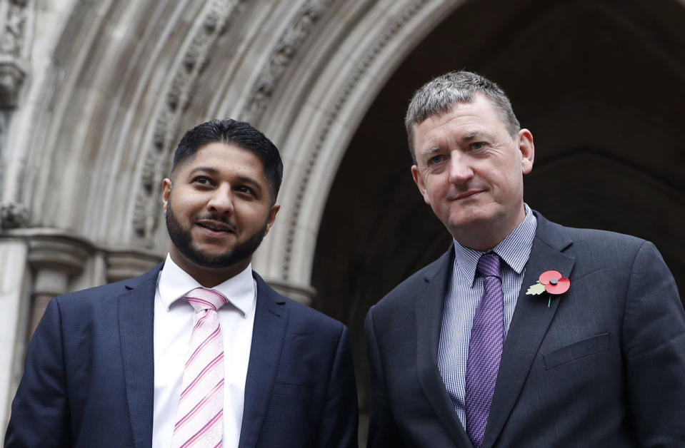 FILE- In this Oct. 30, 2018, file photo, former Uber drivers Yaseen Aslam, left, and James Farrar pose for the media outside the Royal Courts of Justice ahead of a legal hearing over employment rights in London. Uber is giving its U.K. drivers the minimum wage, pensions and holiday pay, following a recent court ruling that said they should be classified as workers and entitled to such benefits, the company announced Tuesday, March 16, 2021. Farrar and Aslam of the App Drivers And Couriers Union said in a statement, the changes stopped short of the Supreme Court's ruling that pay should be calculated from when drivers log on to the app until they log off. And they said the company can't decide by itself the expense base for calculating the minimum wage, which should be based on a collective agreement. (AP Photo/Alastair Grant, File)