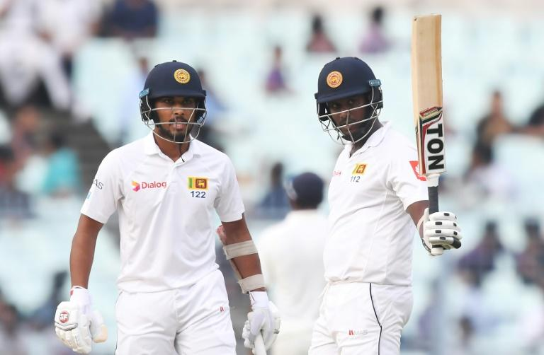 Sri Lanka's Angelo Mathews celebrates after scoring a half-century (50 runs) as captain Dinesh Chandimal looks on during the third day of the first Test between India and Sri Lanka at the Eden Gardens cricket stadium in Kolkata