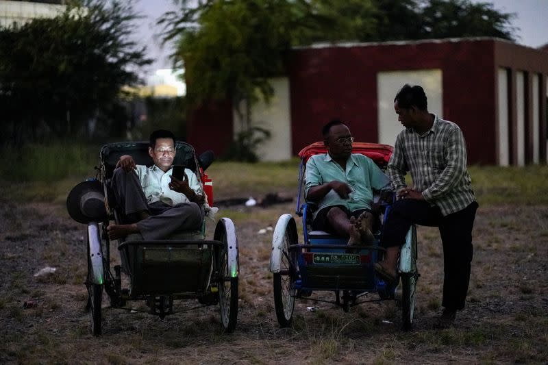Tricycle drivers attend an outdoor movie screening held by a NGO in Phnom Penh