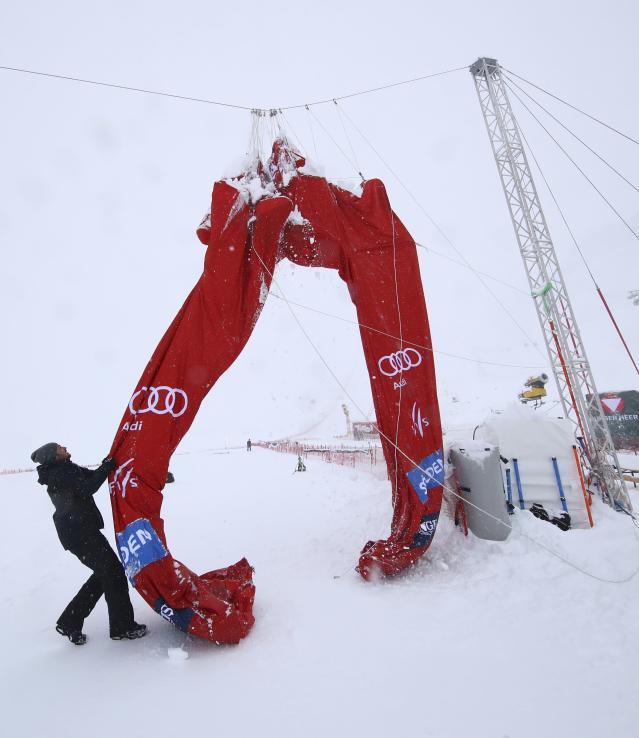 A course crew member pulls on the finish line arch as an alpine ski, men's World Cup giant slalom is canceled due to bad weather, in Soelden, Austria, Sunday, Oct. 27, 2018. (AP Photo/Alessandro Trovati)