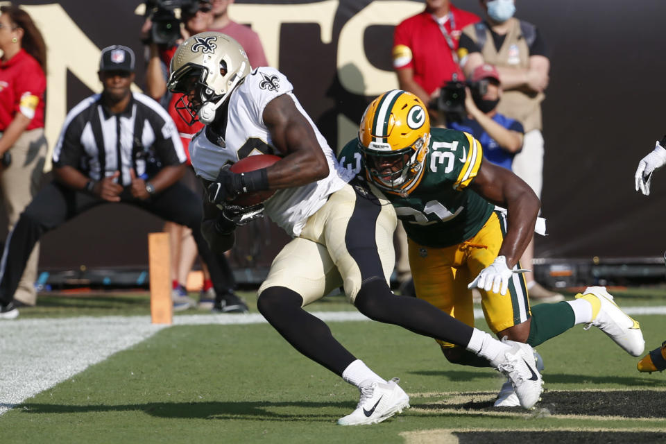 New Orleans Saints tight end Juwan Johnson, left, makes a touchdown reception in front of Green Bay Packers strong safety Adrian Amos (31) during the first half of an NFL football game, Sunday, Sept. 12, 2021, in Jacksonville, Fla. (AP Photo/Stephen B. Morton)
