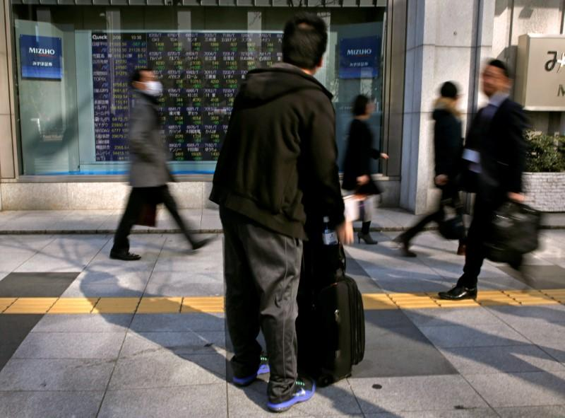 FILE PHOTO: A man looks at an electronic stock quotation board outside a brokerage in Tokyo, Japan February 9, 2018. REUTERS/Toru Hanai/File Photo