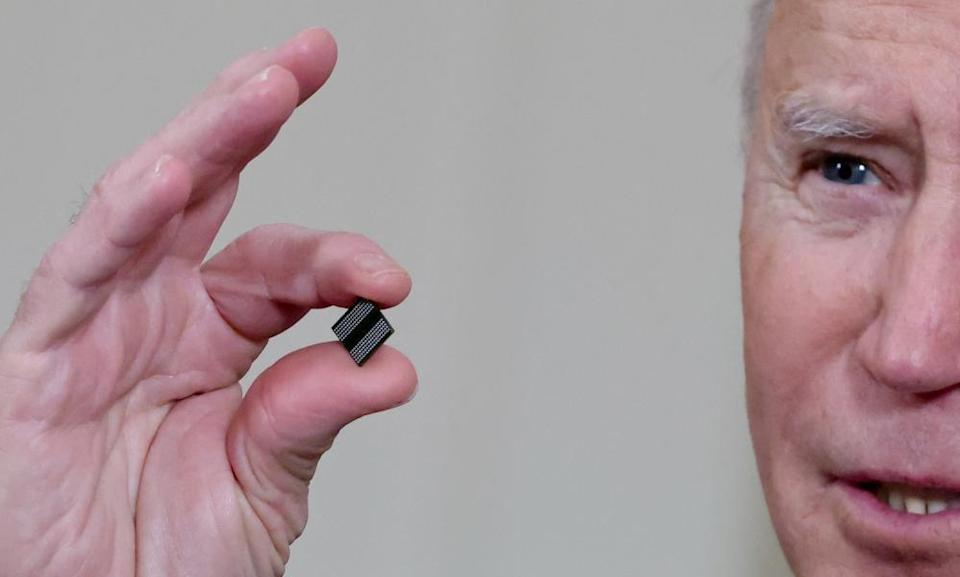 President Biden holds a semiconductor chip prior to signing an executive order aimed at addressing a global semiconductor chip shortage in February.