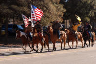 Supporters of President Donald Trump ride horses outside the Statehouse in Santa Fe, N.M., on Wednesday, Jan. 6, 2021, to protest President-elect Joe Biden's electoral victory. (AP Photo/Morgan Lee)