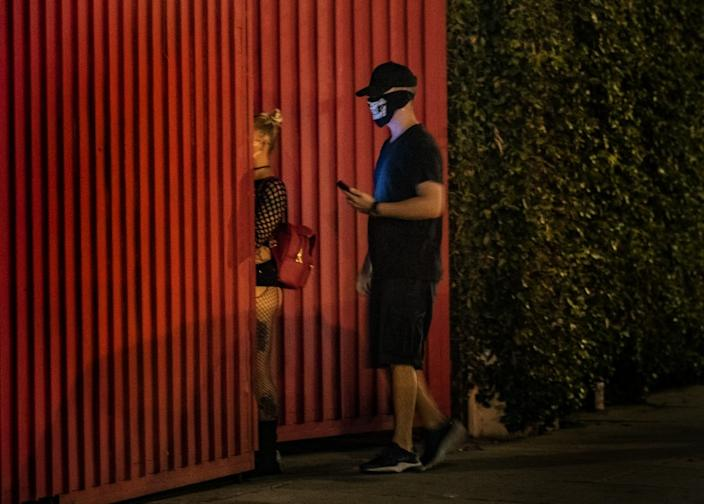 "Masked partygoers pass through a secret gate to attend an underground club Friday. <span class=""copyright"">(Gina Ferazzi/Los Angeles Times)</span>"