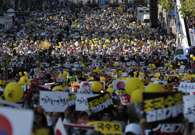 "Pro-government supporters shout slogans before a rally supporting Justice Minister, Cho Kuk in front of Seoul Central District Prosecutors' Office in Seoul, South Korea, Saturday, Oct. 12, 2019. Tens of thousands of government supporters have gathered in South Korea's capital for the fourth-straight weekend to show their support for President Moon Jae-in's controversial justice minister who's enmeshed in explosive political scandal that rocked and polarized the nation. The letters read ""Reform the Prosecution"" and ""Protect Cho Kuk"". (AP Photo/Lee Jin-man)"
