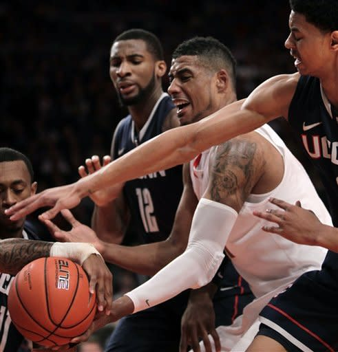 Syracuse's Fab Melo, second from right, battles for a rebound with Connecticut's Jeremy Lamb, right, and Andre Drummond during the quarterfinal round of the Big East NCAA college basketball conference tournament in New York, Thursday, March 8, 2012. (AP Photo/Seth Wenig)