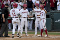 Arkansas batter Cullen Smith (14) is greeted by teammates Cayden Wallace (7), Matt Goodheart (10) and Robert Moore (1) after hitting a grand slam against North Carolina State in the second inning of an NCAA college baseball super regional game Friday, June 11, 2021, in Fayetteville, Ark. (AP Photo/Michael Woods)