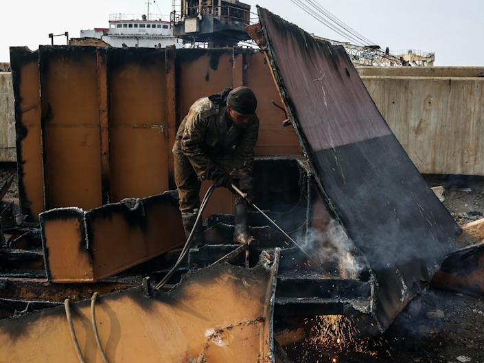 A worker welds a part of an old Ship to get a metal at a shipbreaking yards Kalibaru in Jakarta, Indonesia on September 27, 2018.