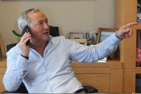 Samih Sawiris, Egyptian billionaire construction tycoon speaks in his mobile phone before an interview with Reuters to discuss his investment plans and outlook for the economy since the flotation of the pound in Cairo, Egypt February 21, 2017. Picture taken February 21, 2017. REUTERS/Atef Hussein
