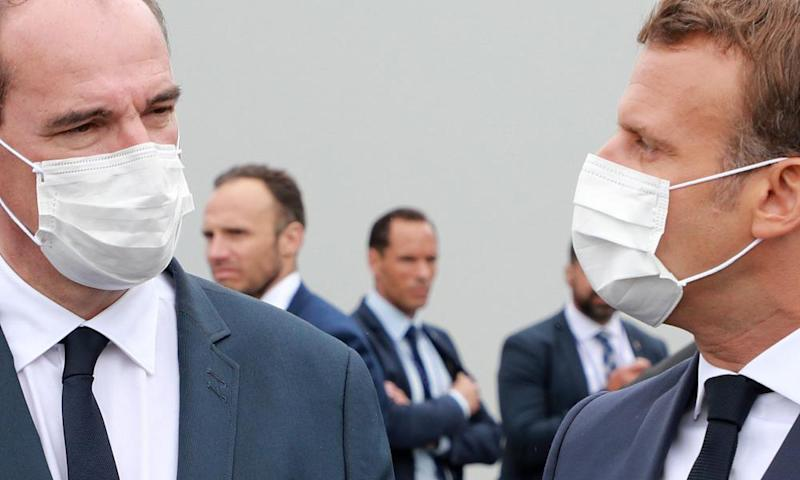 Emmanuel Macron (right) and French prime minister, Jean Castex, both wearing a protective facemasks speak at the end of the annual Bastille Day military ceremony.